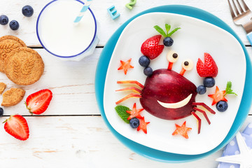 Fun Food for kids. Cute smiling crab made of fresh fruits - apple, strawberry, blueberries and fresh mint - for a healthy breakfast with milk and biscuits