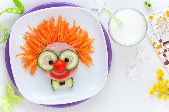 Fun food for kids - cute smiling clown face on ham sandwich decorated with fresh cucumber, carrots and tomatoes for a healthy lunch for children. Creative cooking idea