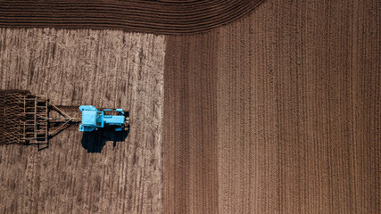 aerial view of tractor , combine cultivating field. drone shot. picture with space for text