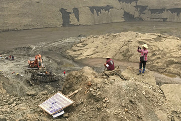 Jade miners take photos atthe mud pond where more than 50 people were killed in collapse, in Hpakant