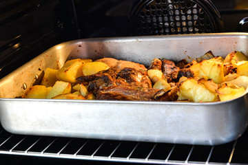 Roast meat with potatoes in aluminum baking dish in the oven.