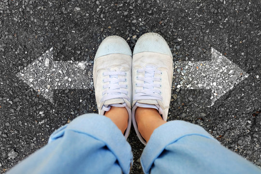 Selfie White Shoes. Woman Wear White Sneakers and Blue Jeans with Two Arrows Different Direction on Concrete Road Background Great for Any Use.