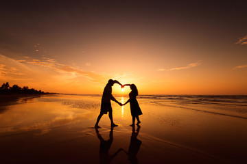 Silhouette of couple making heart shape with arms on beach at sunset