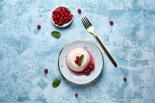 Plate with tasty panna cotta on color table