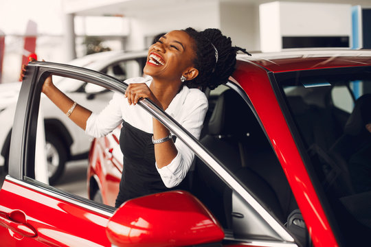 Woman buying the car. Lady in a car salon. Elegant black girl