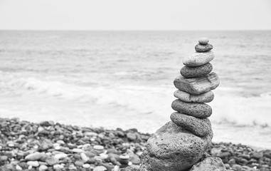 Black and white picture of a stone stack on a beach.