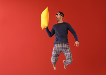Jumping young man in pajamas with sleep mask and pillow on color background