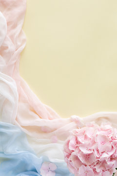 Flowers composition made of pink flowers and pastel scarf. Flat lay, top view, copy space