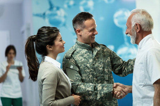 Happy military man shaking hands with senior doctor in the hospital.