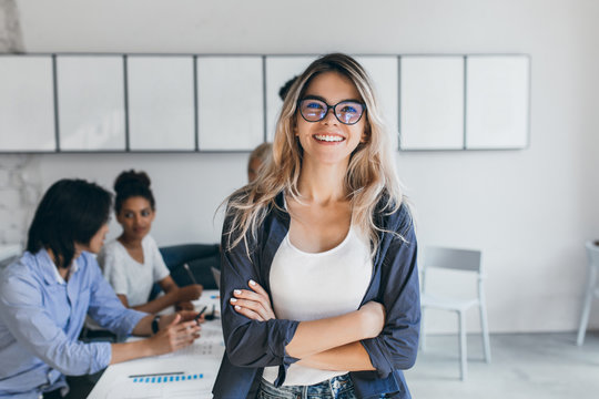 Pleased female secretary in trendy glasses posing in office after meeting with colleagues. Indoor portrait of stylish businesswoman with asian and african workers on background.