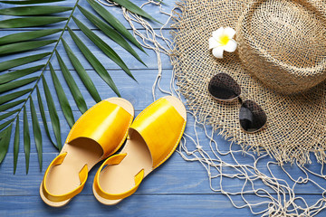 Pair of stylish female sandals, hat, sunglasses and palm leaf on wooden background