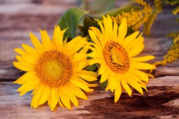 Naturalny bukiet słoneczników i nawłoci na tle drewna