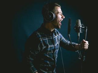 The young guy singing in recording studio Fotobehang