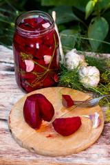 domowe przetwory - słoik z kiszonymi burakami na drewnainym stole wśród warzyw i ziół