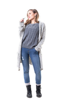Cool happy young woman in long cardigan and sweater using tobacco heating sticks looking away. Full body isolated on white background.