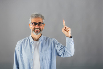 middle aged man shoving index finger on gray background