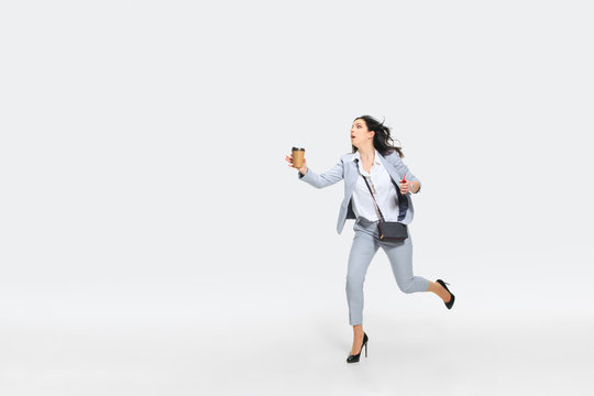 Please, wait. Young woman in gray suit comes late for work while trying to stop the bus on the run. Female model with coffee and smartphone. Concept of office worker's troubles, business, stress out.