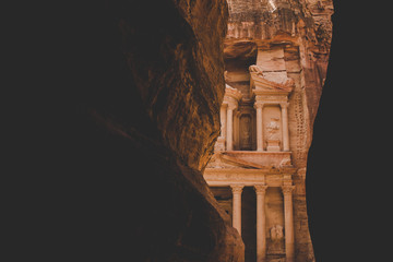 famous world heritage site for tours and sightseeing concept creative picture of Petra treasure ancient architecture building facade carved in sand stone rock, creative foreshortening in dark frame