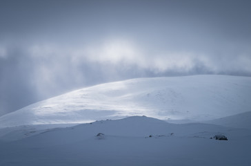 Sunlight shining through the clouds over the snow covered mountains in Sarek,  Lapland. Sweden.