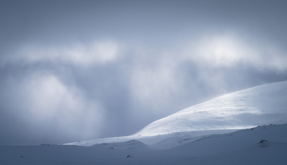 Sunlight shining through the cloudcover over the snow covered mountains in Sarek.  Lapland, Sweden.