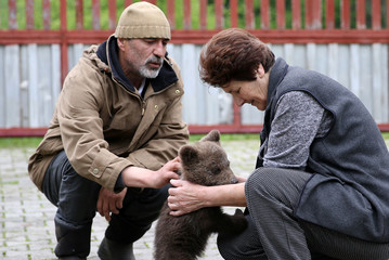 "Zakir Becar and his mother Sija play with an orphaned baby bear named ""Aida"" in front of their house in Gunjani village near Sarajevo"