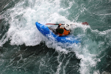 An experienced canoeist paddles while partially submerged in white water rapids.