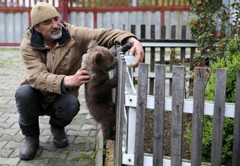 "Zakir Becar feeds orphaned baby bear named ""Aida"" in Gunjani village near Sarajevo"