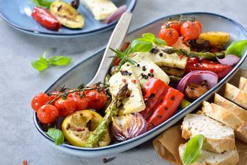 Übergrilltes mediterranes Ofengemüse mit gebackenem Fetakäse auf einem Tisch mit Betonoptik serviert – Grilled mixed mediterranean vegetables with warm feta cheese served on a table with concrete look