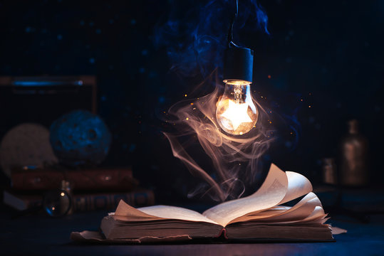 An open book with lighting by a star inside a lightbulb. Night reading conceptual still life with copy space.