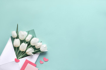Springtime flat lay, white tulips in paper bag on green mint background with envelope, blank cards and decorative hearts