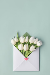 White tulips in paper envelope with decorative heart sticker on light green mint background.