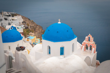 Tilt shift effect of blue dome and rose bell tower in the village of Oia