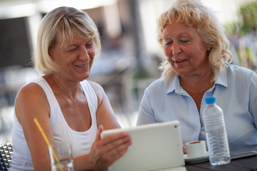 Two smiling senior women are sitting close to each other at a table of an outdoor cafe. They are both looking at the tablet that one of the women is holding in a hand. There are a bottle of water, a
