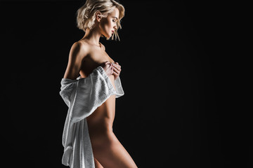 beautiful sexy half-naked young woman in white bathrobe posing isolated on black with copy space