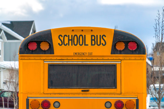 Close up of the rear of a school bus with a window and several signal lights