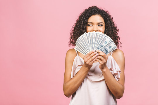 Rich girl! Money winner! Surprised beautiful african american woman in dress holding money and looking at the camera isolated against pink background.