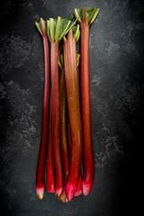 Whole fresh rhubarb steams on dark marble background