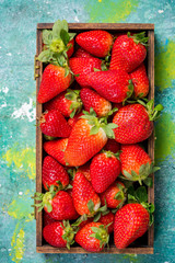 Freshly picked strawberries in wooden box on colorful table