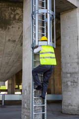 worker in protective wear climbing on metal ladders