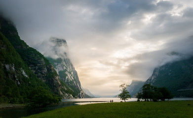 Two women looking out a fjord between high mountains
