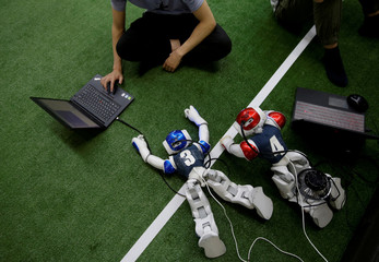 A participant from SJTU team works next to robot soccer players at the break of a competition against SPQR team during the RoboCup Asia-Pacific Tianjin Invitational Tournament 2019 in Tianjin