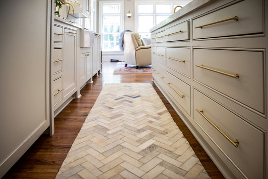 Low view of new renovated kitchen cabinets with Herringbone Runner Rug