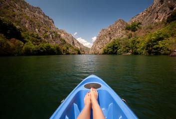 Fototapeta Kayaking through river in Matka canyon, Macedonia. Woman legs in the blue kayak obraz