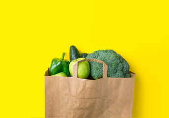 Green raw organic vegetables fruits broccoli cucumbers bell peppers apples in brown paper Kraft grocery bag on yellow background. Healthy diet dietary fiber vegan plastic free concept. Poster banner