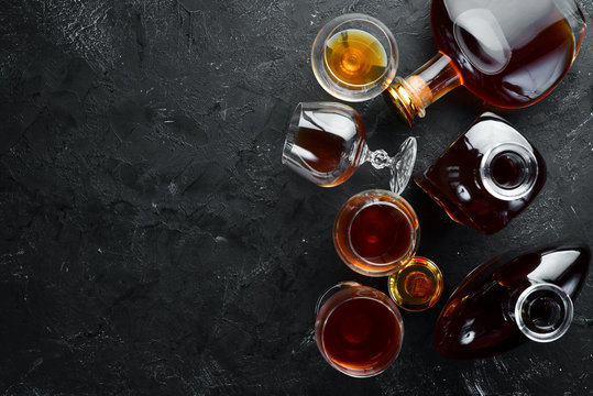 A bottle of cognac and glasses on a black background. Brandy. Top view. Free space for your text.