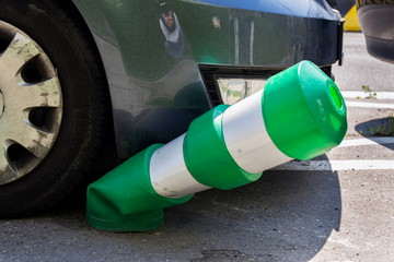 Car bending white and green safety traffic post with front bumper, wrong parking, car insurance, fine, penalty concept