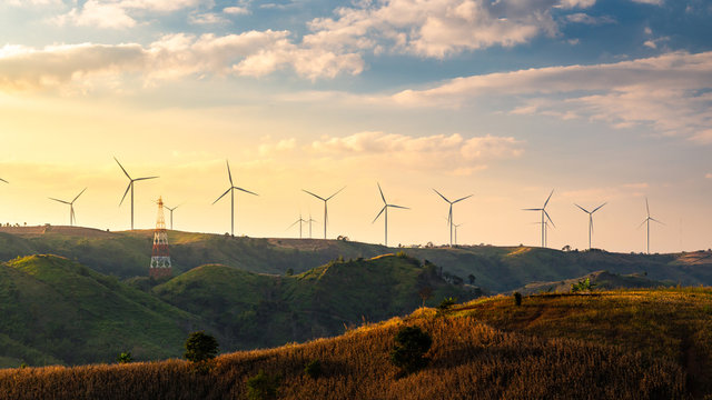 Wind turbines and Orange sunset sky. Beautiful mountain landscape with wind generators turbines,Thailand. Renewable energy concept.