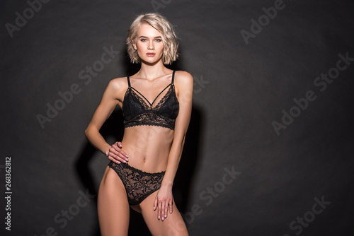 fb23ec92d beautiful sexy girl in lace lingerie looking at camera and posing on black  with copy space