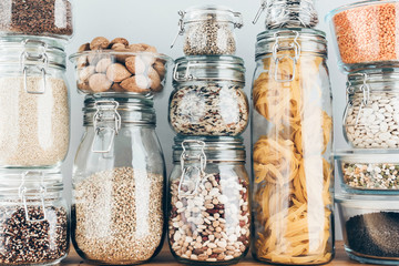 Obraz Assortment of uncooked grains, cereals and pasta in glass jars on wooden table. Healthy cooking, clean eating, zero waste concept. Balanced dieting food - fototapety do salonu