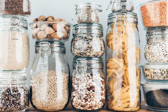 Assortment of uncooked grains, cereals and pasta in glass jars on wooden table. Healthy cooking, clean eating, zero waste concept. Balanced dieting food